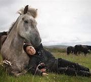 a woman snuggling a horse
